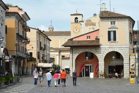 Passers in the historical center of Desenzano del Garda on Lake Garda - Italy. Editorial