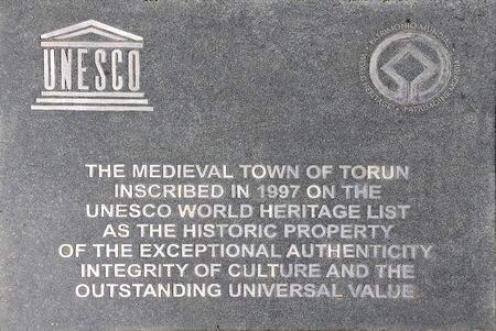 Information board in front of the town hall in Torun about the inclusion of the old town in 1997 in the World Heritage List of Unesco in English - Poland.