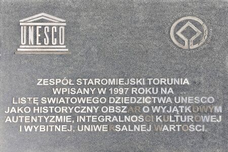 Information board in front of the town hall in Torun about the inclusion of the old town in 1997 in the World Heritage List of Unesco in Polish - Poland.