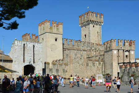 Tourists in front of the Scaligero castle in the historic center of Sirmione on Lake Garda - Italy. Éditoriale