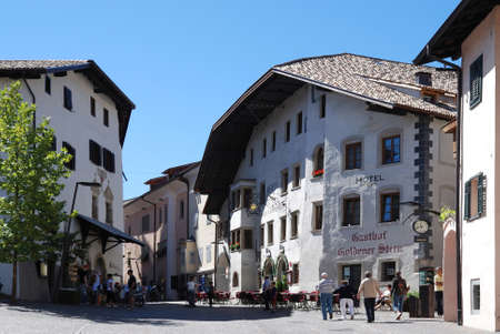 Tourists in Kaltern on the South Tyrolean Wine route in Italy with houses from the 17th century - Italy. Éditoriale