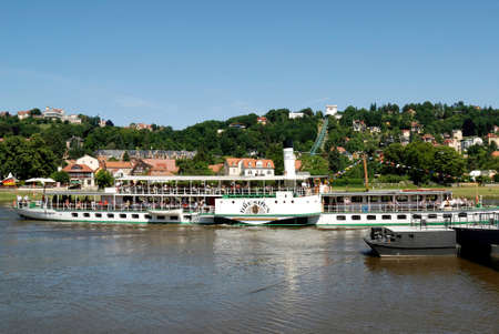 Historical paddle steamer with tourists on the river Elbe in Dresden with the Loschwitzer bridge in the background - Germany.