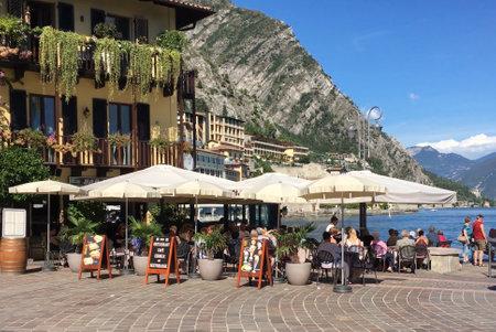 Tourists walking on coastal promenade in Limone sul Garda on the shore of Lake Garda - Italy. Standard-Bild - 167047065