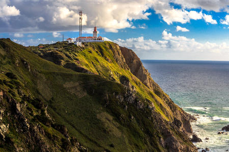 The lighthouse in Cabo da Roca. Cliffs and rocks on the Atlantic ocean coast in Sintra in a beautiful spring day, Portugal
