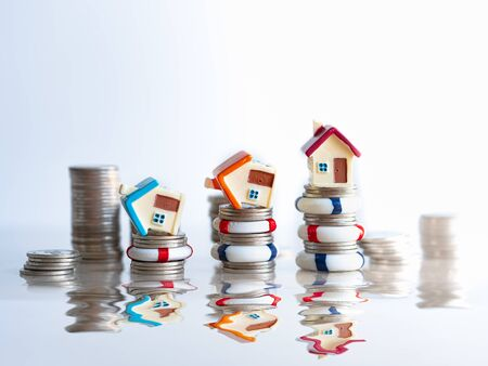 Home insurance concept. House model in lifebuoys on coins stack. Securing large value of home by applying an insurance, insured home safe. structural risk as security from hazards like flooding fire.