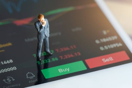Miniature people: Businessman standing on mobile phone, chart, numbers and sell and buy options. red and green candlestick chart and stock trading smartphone screen background.
