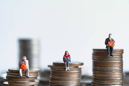 Miniature people: Elderly people sitting on coins stack. Retirement planning. money saving and Investment. Time counting down for retirement concept. Banque d'images
