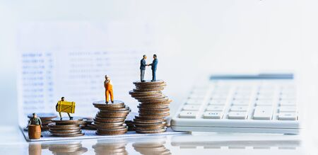 Miniature people standing on a pile of coins. Inequality and social class. Income and economic inequality concept. Inequality in social class, ideology, Gender, Racial and ethnic and health.