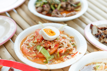 Thai Style Papaya Salad with Satled Eggs on wood table in local Thailand