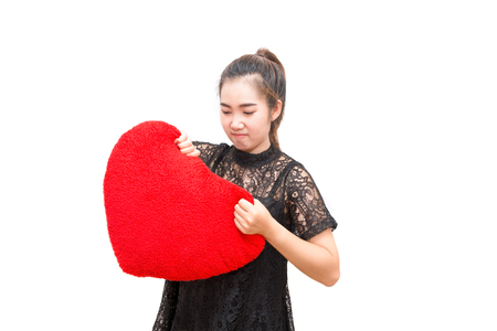 Broken heart woman is angry and try to tear heart pillow on isolated white background Stock Photo