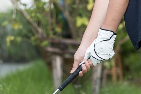 Golfer dragen witte handschoen holdiing golf club met twee handen