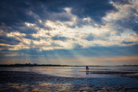 crepuscular: Kissing lovers on the beach under twilight crepuscular rays Stock Photo