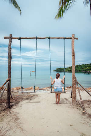 The scenery of a lonely woman sitting on a swing at Koh Kood island in Trat province, Thailand. Stock Photo
