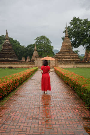 The scenery of a woman with her Lanna style umbrella walking in Wat Mahathat temple on a cloudy day in the rainy season at Sukhothai province, Thailand.