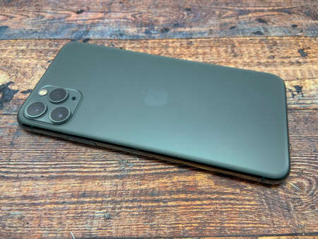 BALI, INDONESIA JUNE 29, 2020: Iphone 11 Pro Midnight Green It has been used on a table with a wooden texture, top view. latest iphone products.