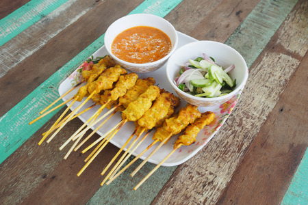 satay sauce: Pork satay sauce and side salad on a plate. Vintage wooden table Stock Photo