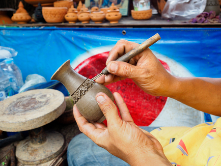 artist: The artist is carved vases from clay before being taken to the furnace.