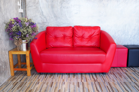 Red sofa in a room with wood tiled floors, the back wall is a cement, sideways put a vase of flowers. Stock Photo