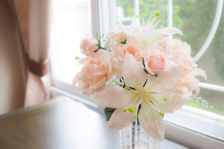 Flowers in a Glass Vase on table near window. Banque d'images