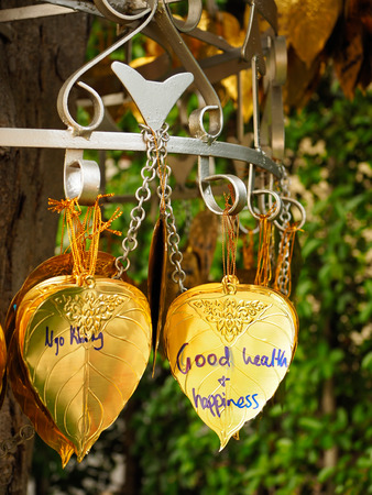 Write your wishes on the Gold Bodhi hung on a metal rod under the tree. Stock Photo
