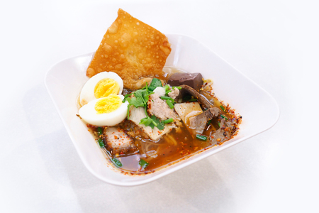 Spicy tom yum noodle with egg, pork and fried dumpling.