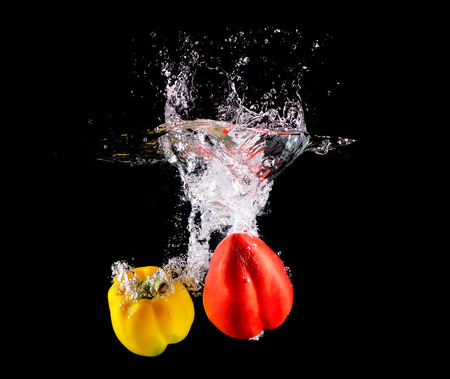 Fresh Bell pepper making splash in water.