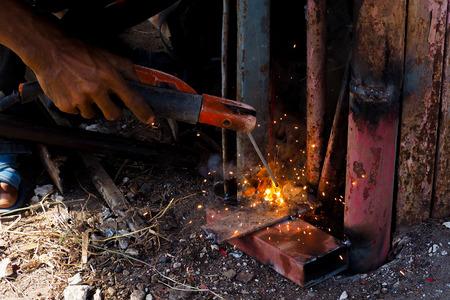 Arc welding and welding fumes, Worker welding on steel in the job site. Stock Photo