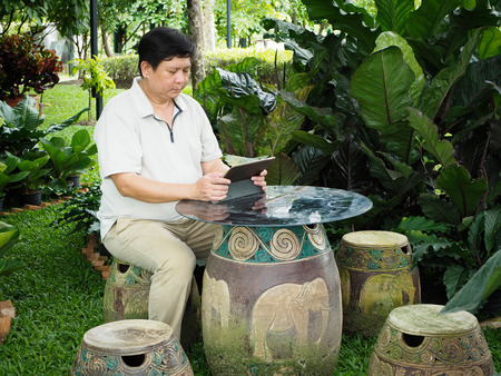 Man finishing work on his tablet and relaxing in the garden.