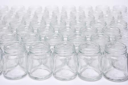 Short glass bottle no cap many glasses row, on white background. Standard-Bild