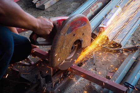 The worker in the workshop cut the steel tube angle grinder, cutting tube.