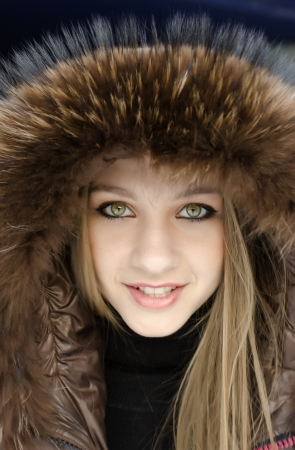 portrait of a young smiling girl in a jacket with a hood photo