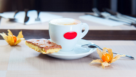 custard slices: chocolate cake on a plate with cup of coffee and berry Stock Photo