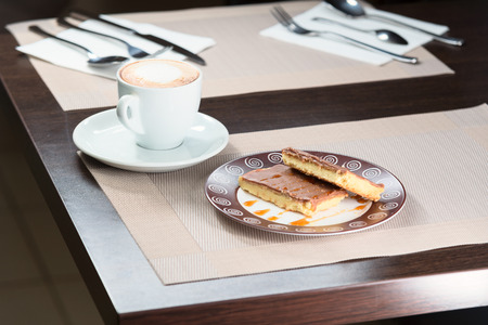 custard slices: chocolate cake on a plate  poured syrup and cup of coffee