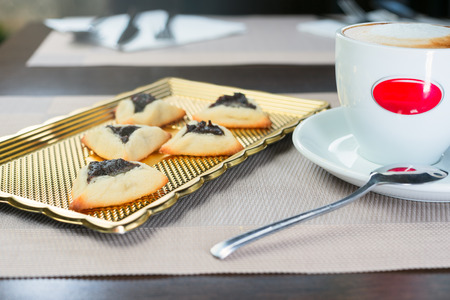 prunes: homemade cookies with prunes lying on a tray next to a cup of coffee