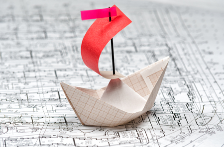 paper boat floating on the waves of a paper drawing Stock Photo