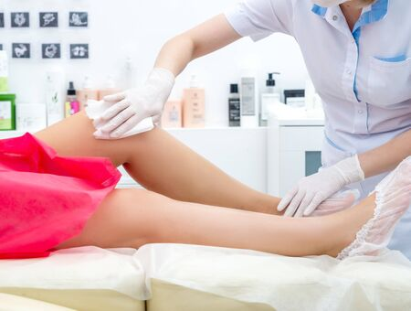 beautician hair removal procedure on the clients feet in beauty parlor