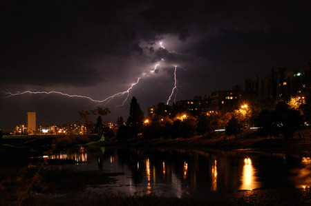 Lightning and thunderstorm in the city with reflection in water of river