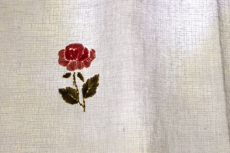 stitching of a red flower on a cotton curtain.