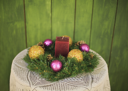 Christmas wreath with a candle and Christmas balls on a table with a beautiful tablecloth on a green background.