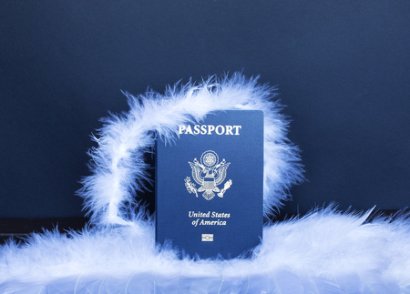 United States Passport on the wings of an angel on a black background. The dream of American migration. Americas voluntary mission with other people or countries.