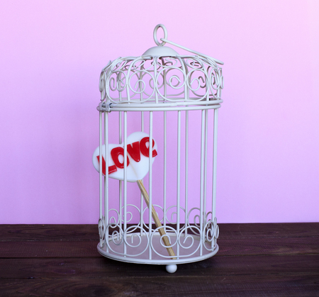 Heart in a cage on a pink background. The concept of love, Valentines Day. Forced love. Blind love. Forced love.