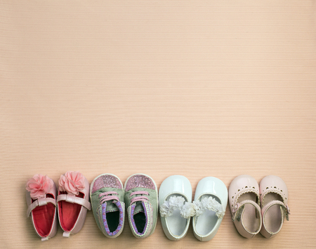 Many cute baby shoe placed on pink background , top view. shoes for girls. Concept of children's clothing.