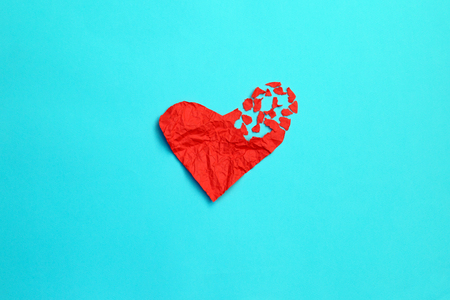 Broken heart breakup concept separation and divorce icon. Red crumpled paper shaped as a torn love on blue background. Symbol of medical cardiovascular health care problems due to illness