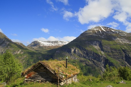 Old wooden house with grass roof in Norway. Norwegian typical grass roof country house in scandinavian panorama