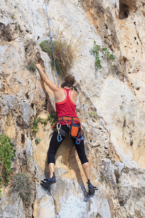 A young woman with a rope engaged in the sports of rock climbing on the rock in Nafplio, Greece.