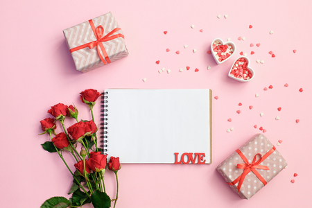 Notebook with gift box, flowers and hearts on a pink background. Valentines day background. Space for text, top view. Writing romantic letters. Mother Day, Wedding Day, March 8 Archivio Fotografico