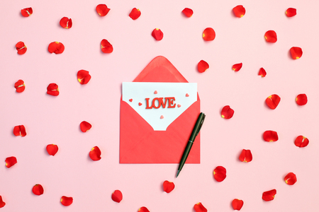 Envelope rose petals and red hearts on pink background. Love concept. Saint Valentine Day concept. Mother day concept. Foto de archivo