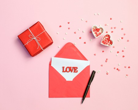 envelope, pen, gift box and red hearts on pink background. Love concept. Saint Valentine Day concept. Mother day concept.