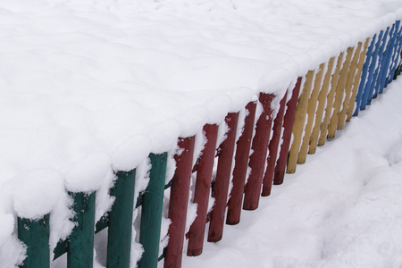 snow on a wooden fence as a background image. Winter at countryside with a snowy old wooden fence, surrounded by a thick layer of snow. Rustic color wooden fence covered with snow