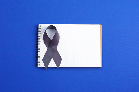 Brain cancer, symbolic bow color for Brain tumor, Allergies, Alpha-1 Antitrypsin Deficiency, Aphasia, Asthma, Borderline Personality Disorder. grey ribbon and open notebook on blue background,